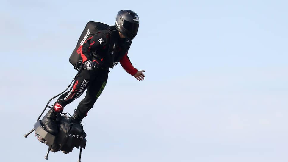 Летающий человек во время полета на «летающей доски» с реактивным мотором Flyboard